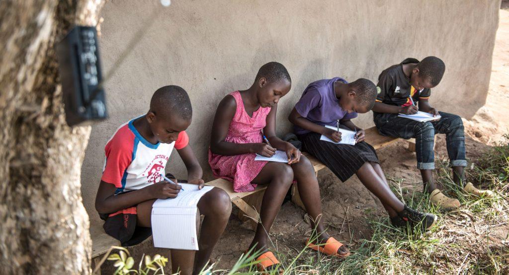 Neljä ugandalaista koululaista istuu penkillä keskittyneenä kirjoittamaan vihkoihinsa
