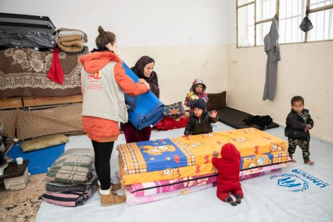 Avustustyöntekijä auttaa äiti levittämään patjoja pienten lasten pyöriessä ympärillä.