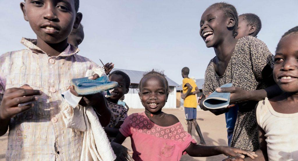 Iloisia lapsia, osalla kouluvihot käsissä.