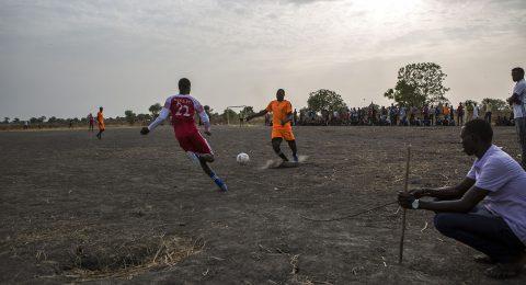 Jalkapallo-ottelu, jossa punaiseen ja oransiin pukeutuneet pelaajat taistelevat pallosta