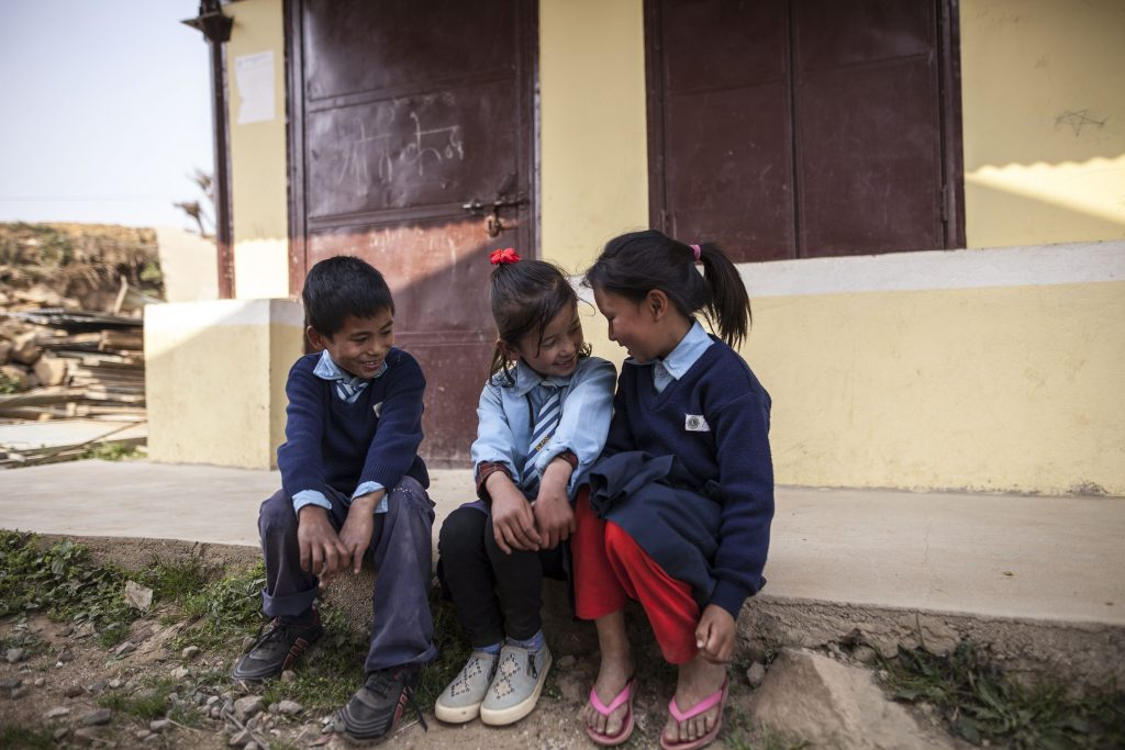 Kolme pientä nepalilaista koululaista istuu rakennuksen edessä portailla.