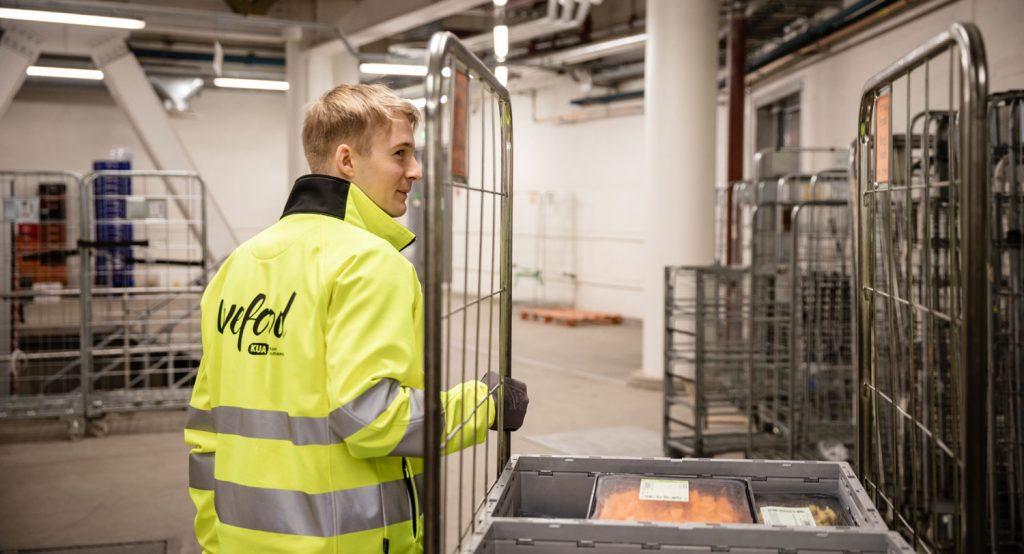 WeFood-takkiin pukeutunut hymyilevä henkilö kuljettaa rullakkoa varastossa