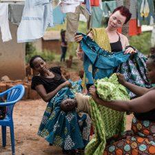 Ompelijayrittäjä Ahimidwe Boutros tarkastelee vaatteita ulkona asiakkaiden kanssa