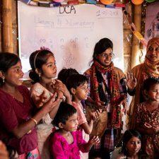 Iloisia naisia ja lapsia valkotaulun edessä.