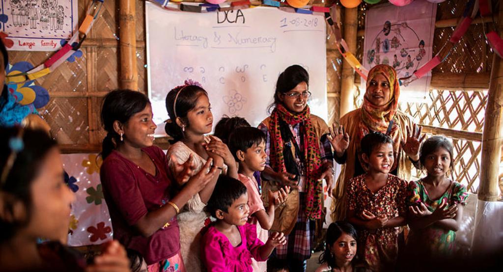Joyful women and children in front of a whiteboard.