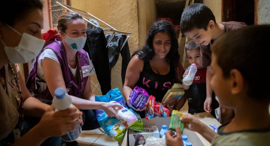 Lapsiperhe ja avustustyöntekijä avonaisen hygieniatarvikelaatikon äärelllä.