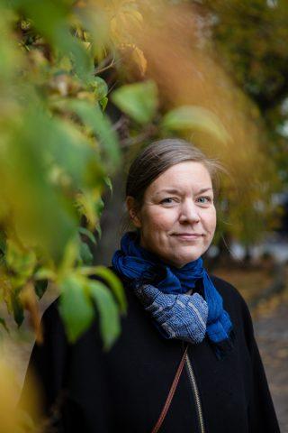 Nainen seisoo puistossa syksyisten lehtien keskellä.