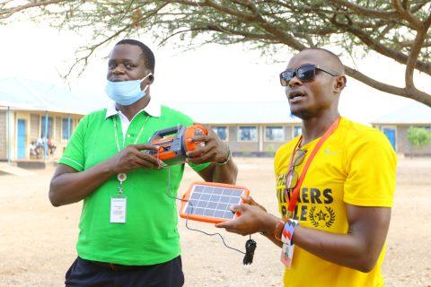 Kaksi miestä pitelee aurinkopaneelia ja radiota käsissään koulun pihalla.