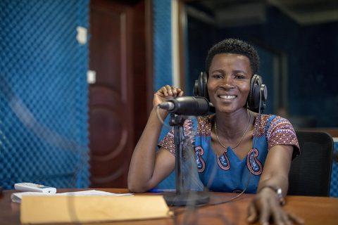 nainen istuu studiossa kuulokkeet pääsä ja hymyilee kameralle. Etualalla mikrofoni.