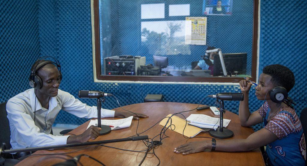 Mies ja nainen istuvat studiossa pöydän molemmin puolin mikrofonit edessään ja kuulokkeet päässä.