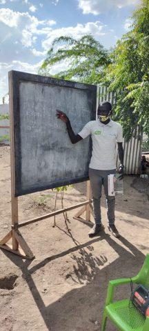 Mies osoittaa tekstiä liitutaululla kasvomaski kasvoillaan.