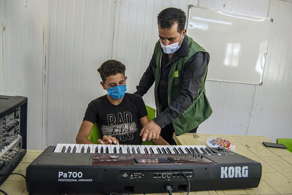 Musiikinopettaja ohjaa Mohammad Al-Ahmadin harjoittelua.