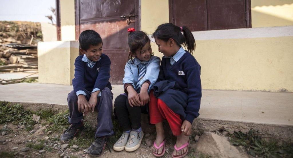 Kolme lasta istuu rakennuksen edessä rappusella.