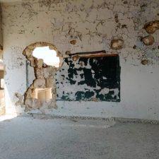 Luokkahuone, jonka seinissä on suuria reikiä pommien jäljiltä.