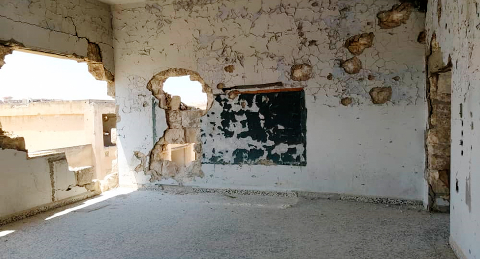 A class room with big wholes in the walls.