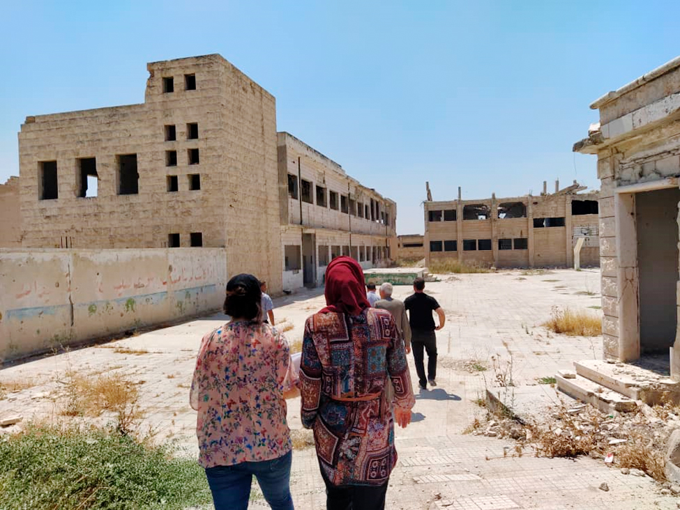 People walking on scoold yard. School buildings in the background are damaged by the war.