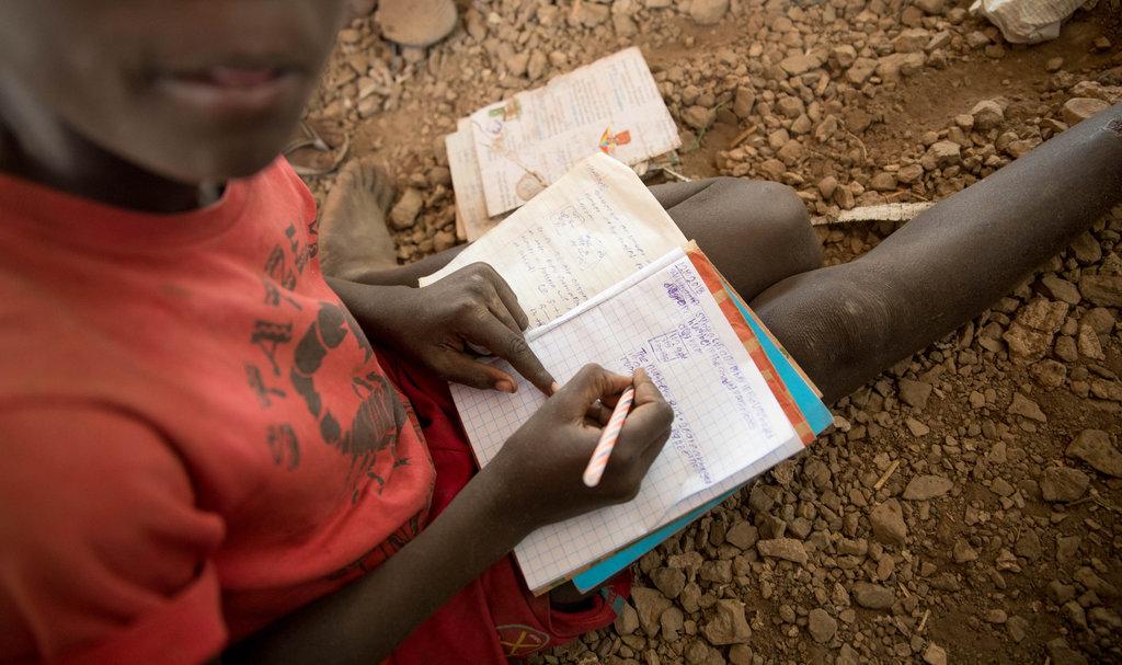 Lapsi istuu maassa ja kirjoittaa vihkoon.