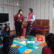 Naisia istuu lattialla ringissä ja kaksi seisoo puhumassa muiden katsoessa.