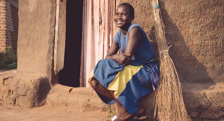 Nuori tyttö istuu kotinsa edustalla.