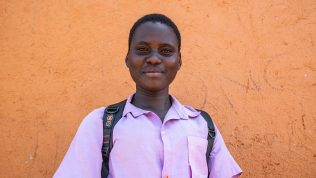 Tyttö seisoo reppu selässä koulun edessä.