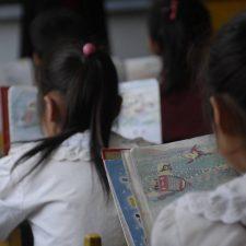 Pieniä koululaisia lukemassa luokkahuoneessa.