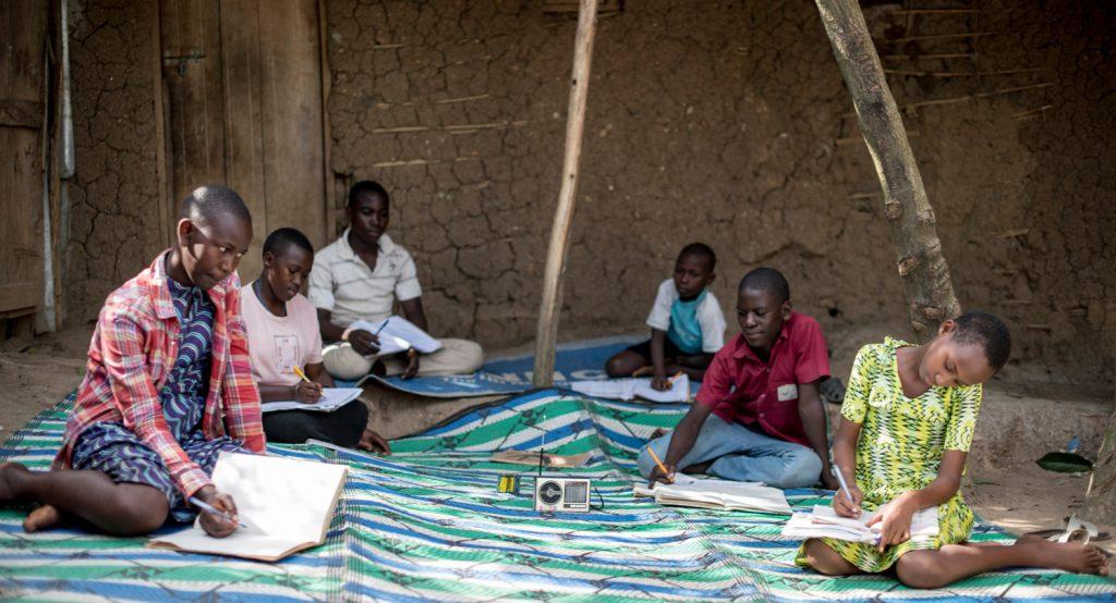 Lapsia talon edustalla kuuntelemassa radio-opetusta ja kirjoittamassa vihkoihin maahan levitetyllä kankaalla talon edustalla.