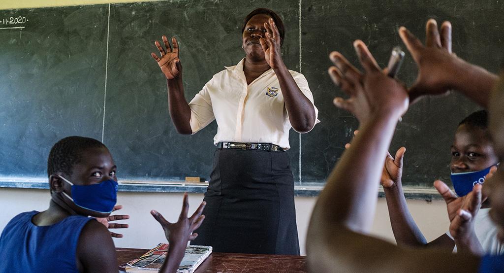 Opettaja Bazio Rose Ajax opettaa viittomakieltä luokan edessä.