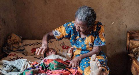 Vanha nainen silittää sängyssä makaavaa pientä lasta