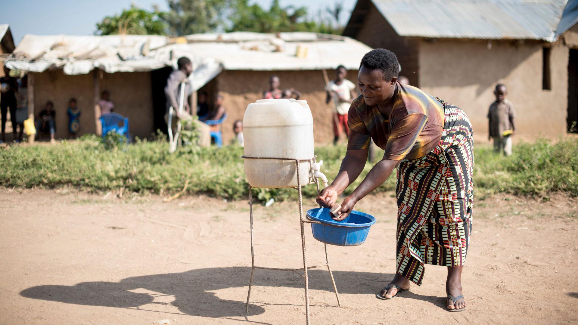 Nainen pesee käsiään käsienpesupistellä pakolaisalueella