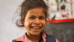 Tyttö hymyilee leveästi koululuokassa