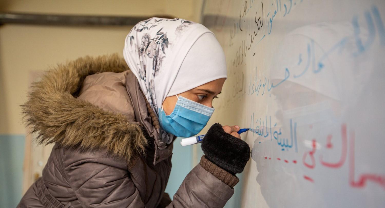 Tyttö kirjoittaa tussilla taululle maski kasvoillaan