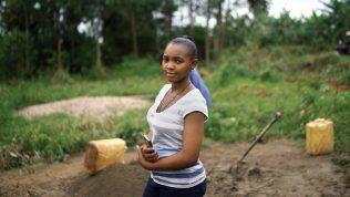 Nuori nainen hymyilee kameralle seistessään pellolla.