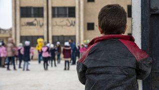 Poika seisoo selin kameraan ja katsoo pihalla leikkiviä koululaisia kohti