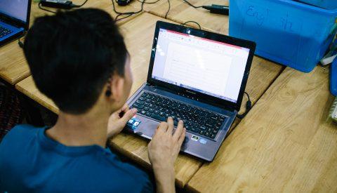 Myanmarilainen nuori mies työskentelee kannettavalla tietokoneella.
