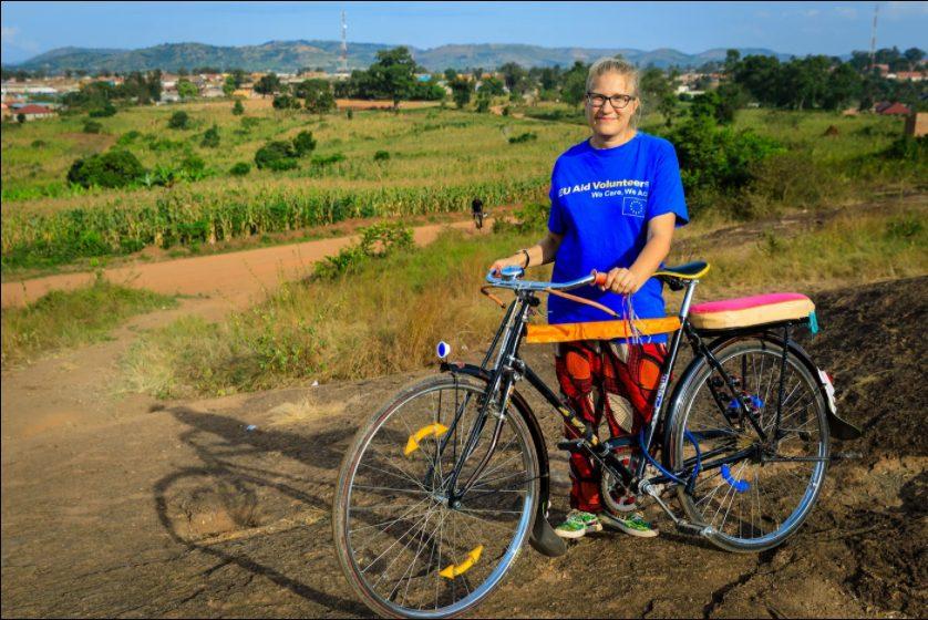 EU Aid -vapaaehtoinen seisoo polkupyörän kanssa vehreällä mäellä.