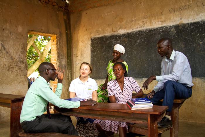 OIR-vapaaehtoinen keskustelee kolmen ugandalaisen opettajan kanssa luokkahuoneessa.