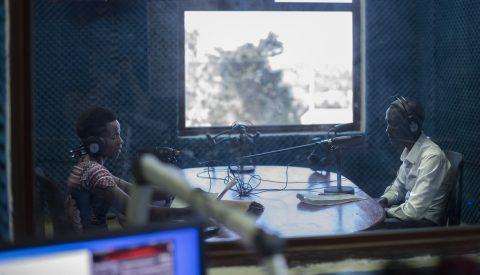 Kaksi opettajaa puhuu mikrofoneihin kuulokkeet päässä lasiseinän takana.