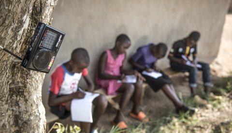 Etualalla radio, jota penkillä istuvat neljä lasta kuuntelevat ja kirjoittavat vihkoon.