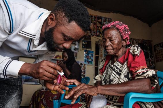 Mies hoitaa vanhan naisen kynsiä.