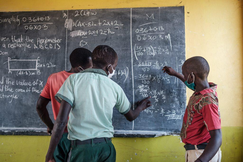 Kolme lasta kirjoittaa liitutaululle.