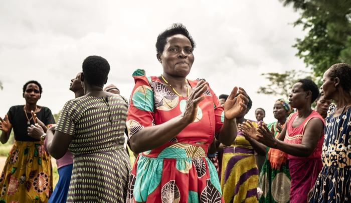Hymyilevä nainen taputtaa käsiään tanssivien naisten keskellä.