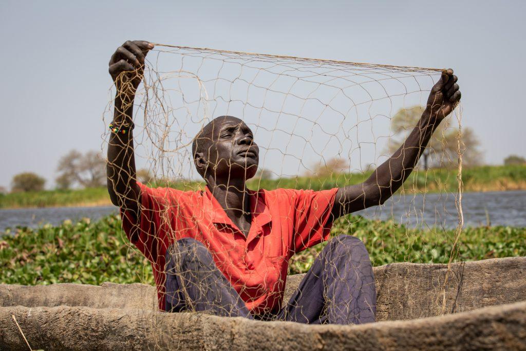 Mies tarkistaa kalaverkkoa.