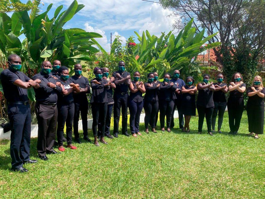 Ugandan maatoimistomme osallistuu kampanjaan poseeraamalla pihalla mustiin pukeutuneina.