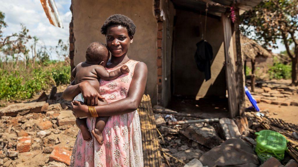 Nuori nainen sisarensa neljän kuukauden ikäisen lapsi sylissään talon edustalla