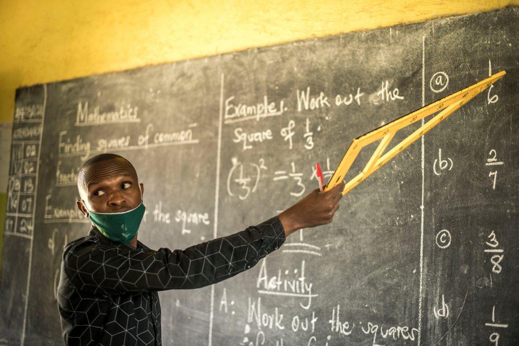 Felix Tumwesigye points to something on the blackboard and looks back at his students.