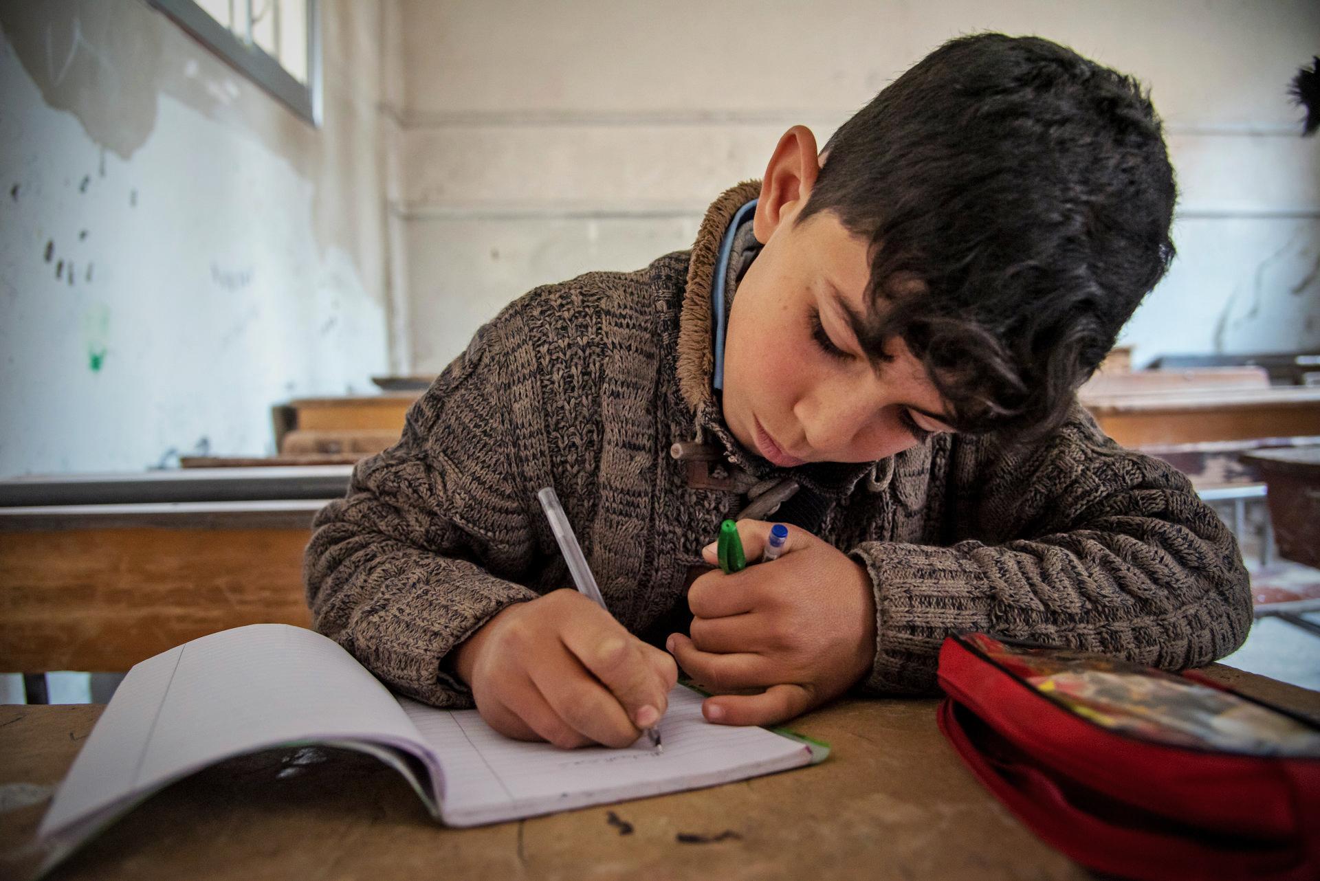 Poika kirjoittaa vihkoon luokassa.