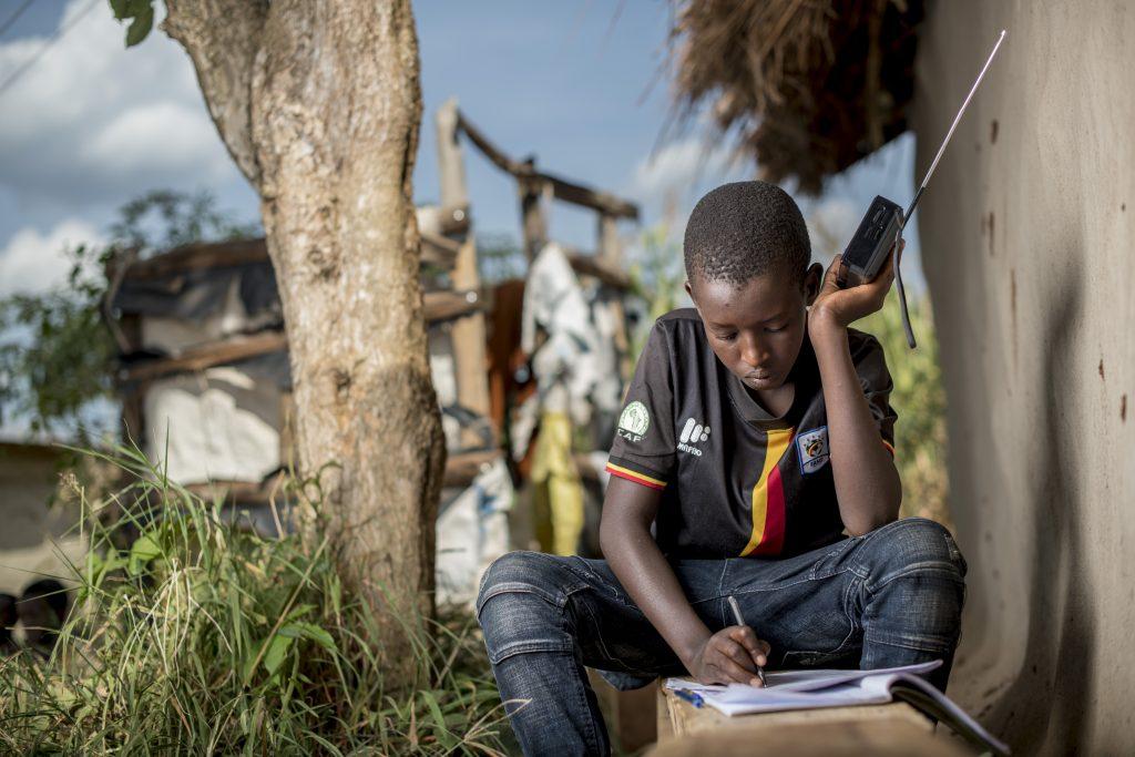 Poika istuu ulkona pidellen matkaradiota korvalla ja kirjoittaa  vihkoon.
