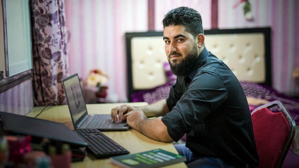 Mies istuu tietokoneen ääressä.