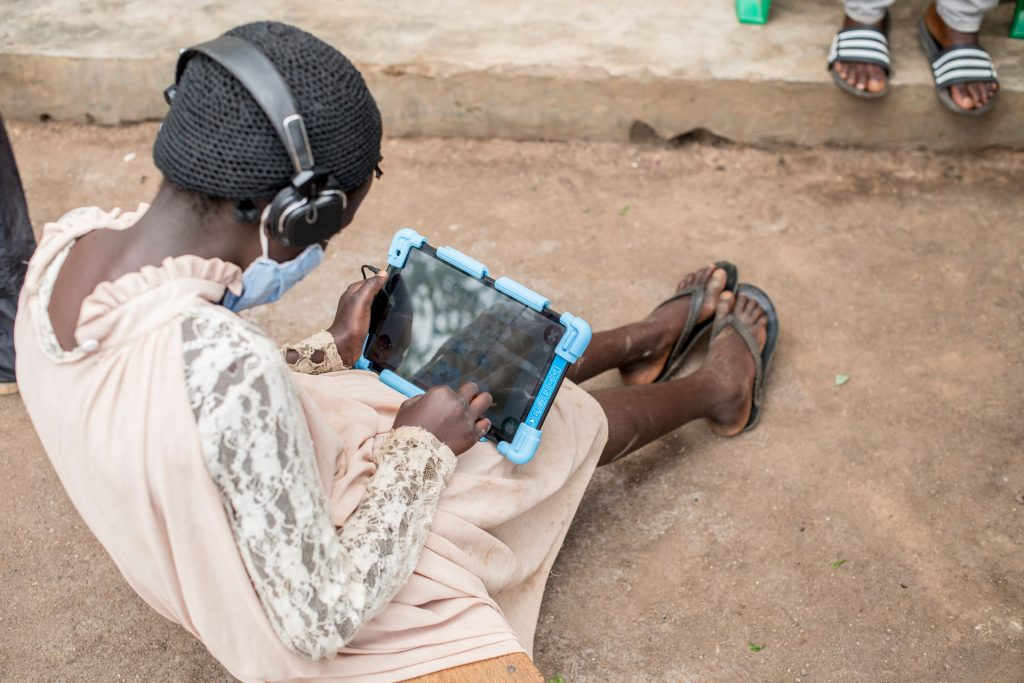 A girl sits on the ground studying with a tablet.