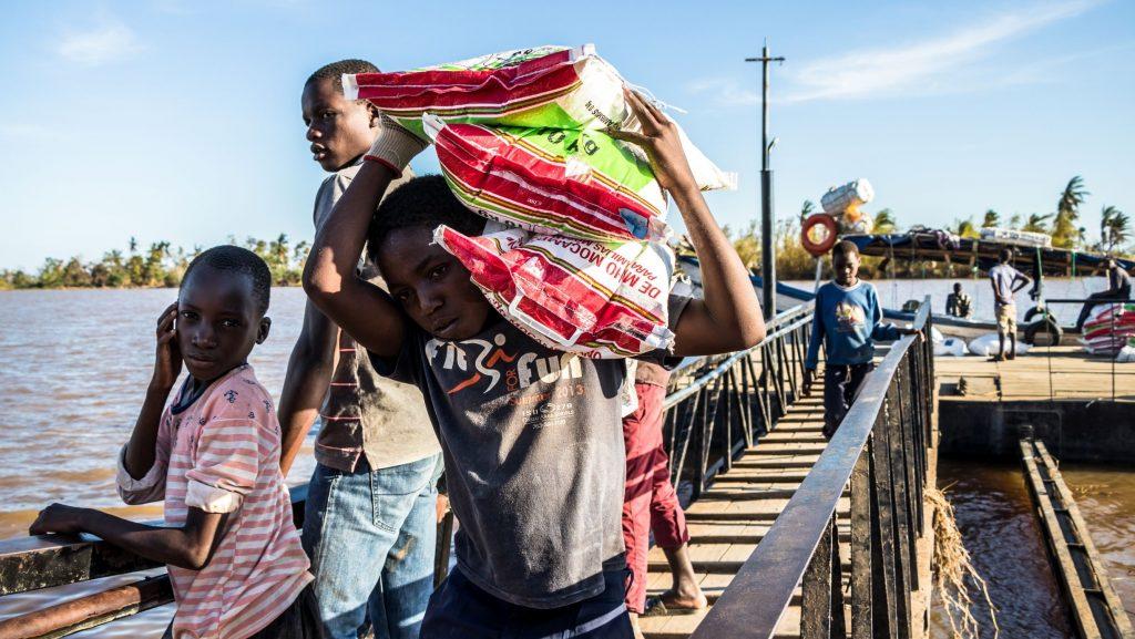 Poika kantaa toisella olallaan kolmea isoa säkkiä veneestä, joka on juuri saapunut Buzin kaupunkiin